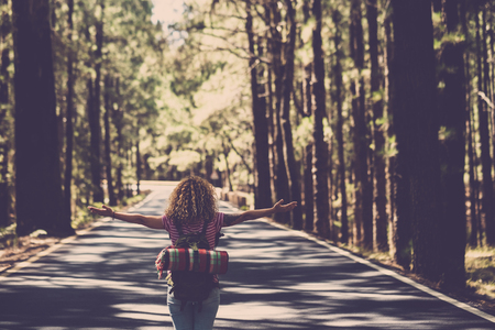 Eternity and success satisfaction life concept with lonely girl curly hai rin the middle of long road in the forest with open arms and backpack - wanderlust and travel style people Stockfoto - 118102353