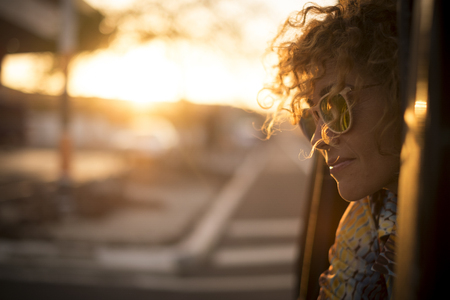 Beautiful sunny sunset time portrait for cute lady smiling and enjoying the feeling with the freedom outdoor - curly hair in the wind and sunglasses for travel concept image Stock Photo