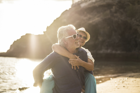 adults caucasian people couple in love with man carrying the woman and both smile and laugh a lot - sunset and backlight at the beach - vacation lifestyle married forever concept for happy matures retired
