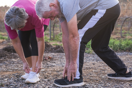 Couple of senior adult caucasian people man and woman doing fitness running exercises outdoor to stay healthy and hace care of their bodies - wellness and sport lifestyle concept Stok Fotoğraf