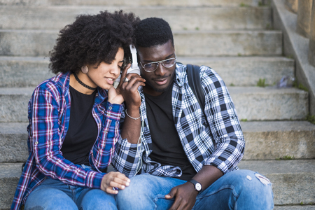 Young couple listening music from one shared headphones in friendship and relationship - feeling and love for girl and boy - first date concept - diversity with afro american people with hipster style 版權商用圖片