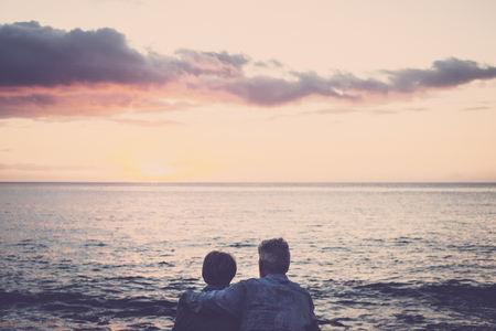 elderly couple sitting and hugging each other looking at the sea at sunset relaxing. Concept of vacation, leisure time, relaxation. Love for caucasian adult people together with hug and relationship lifestyle outdoor concept