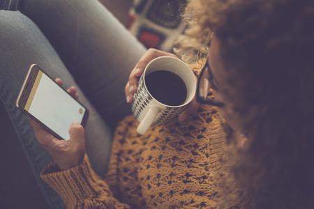 Warme Heimatmosphäre für eine Dame mittleren Alters, die mit einer Hand die Internettechnologie des Mobiltelefons verwendet und eine Tasse Kaffee trinkt und eine Pause macht - Draufsicht der Frau zu Hause Standard-Bild