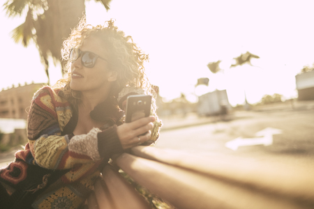 Pretty caucasian woman sitted on the road with mobile phone