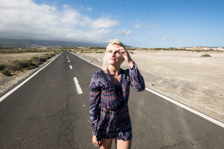 Beautiful attractive caucasian girl walk with a fashion dress on a long way road - horizon and travel concept with airplane flying in the background. and asphalt to infinite - future for people concept