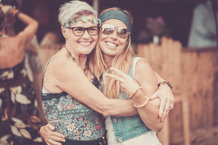 Two different ages females friends hug and stay in love together with smile and fun - cheerful different ages caucasian people - mother and daughter - happy  hippy people in vintage color filter Banque d'images