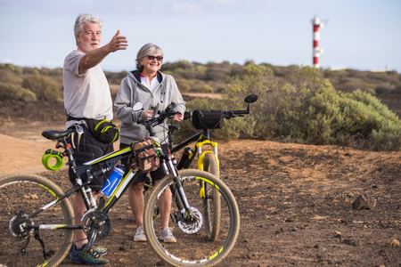 Cheerful caucasian adult senior couple with mountain bike doing healthy sport outdoor leisure activity together - Old people enjoy elderly riding in the nature and enjoying lifestyle Banco de Imagens