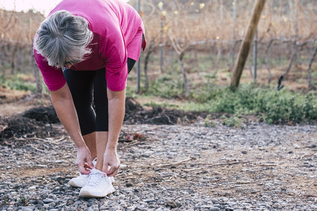 Senior adult caucasian people woman doing fitness running exercises outdoor to stay healthy and hace care of their bodies - wellness and sport lifestyle concept Stok Fotoğraf