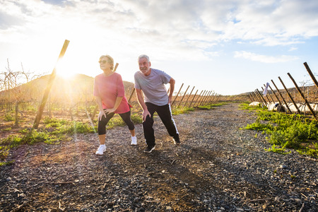 Two mature people man and woman enjoying sport fitness activity outdoor in the nature countryside at sunset doing stretching and balance exercise - wellness and healthy lifestyle for aged couple