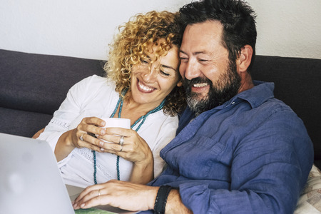 Cheerful beautiful happy caucasian couple middle age at home sitting on the couch using a technology device laptop  - internet and leisure activity indoor for people smiling and enjoying the time