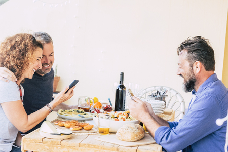 Three caucasian friends eating at the restaurant each one looking the phone and not speaking with the others - internte cellular addicted people - bad use of technology concept 版權商用圖片