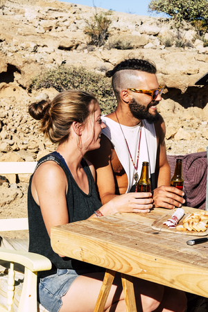 Couple taking a beer together in relationship in outdoor country side location place - alternative hipster traveler people enjoying the sunny time in summer - rural concept Stock Photo