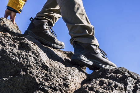 Close up of hiker legs and shoes rocking the mountain helping with one hand - concept of outdoor leisure activity and sport lifestyle - adventure and difficult enjoying the open air