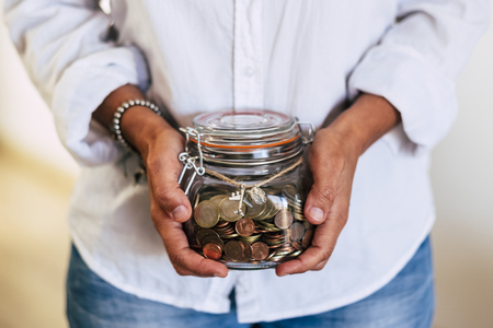 Close up of woman hands at home taking a transparent glass vase full of coins and airplane outside - economy and money for the next travel vacation - familiar business concept Stockfoto