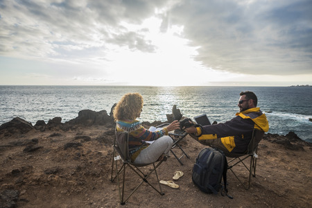 Nomadic couple working with laptop outdoors on the cliffs 版權商用圖片