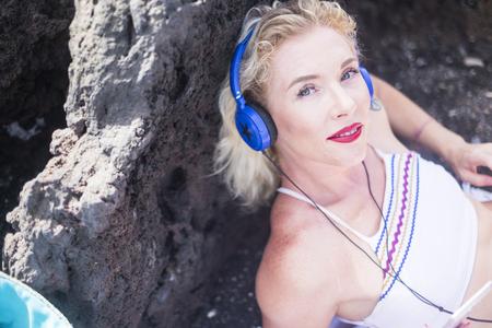 Bonita mujer joven de mediana edad mirando sonriendo a la cámara mientras escucha música con auriculares azules con estrella - lápiz labial rojo y ojos azules gente caucásica disfrutando del aire libre Foto de archivo