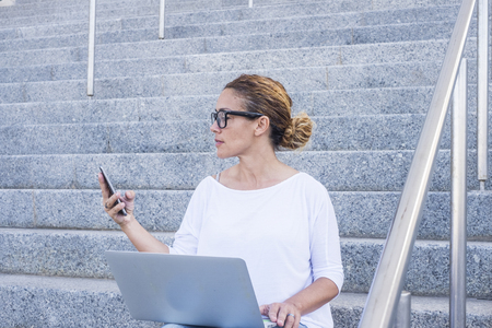 Business woman beautiful female working with phone device and laptop computer aoutdoor witting on a urban stairs in the city - digital nomad and freelance - freedom to work outdoor and enjoy modern happy lifestyle