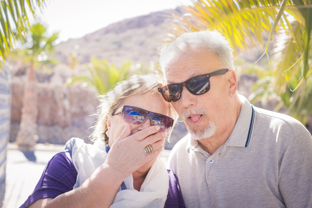 Senior adult caucasian people having fun together - nice faces laughing for an elderly couple in vacation. Palms and sunlight and they wear sunglasses. Nice and funny life concept.