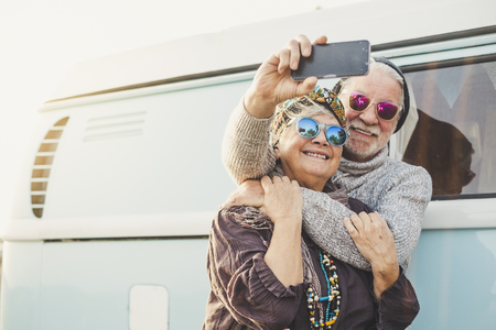 70 anni allegra coppia adulta felice scatta una foto selfie fuori da un furgone blu intage con tecnologia moderna - concetto di turismo e turismo per le persone che amano viaggiare insieme in una relazione per sempre - felicità in pensione Archivio Fotografico