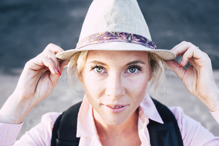 Beautiful european middle age young woman with blue green eyes looking at the camera holding a fashion hat - bright image for attractive people in outdoor leisure activity