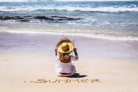 Summer vacation holiday concept with people - white dress tourist woman sit down at the beach on the sand looking the blue waves from sea and holding the hat - summer write on the sand 스톡 콘텐츠