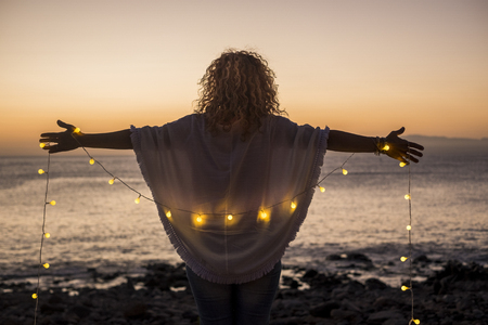 Enjoying freedom and nature concept with curly blonde woman viewed from back with open arms to hug the nature and ocean during romantic vacation and travel lifestyle - yellow articifial lights Imagens