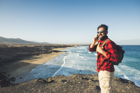 Standing caucasian man calling at the phone on a isolate cliff with ocean waves view - backpacker alternative lifestyle vacation for people love nature and outdoors - technology and adventure concept