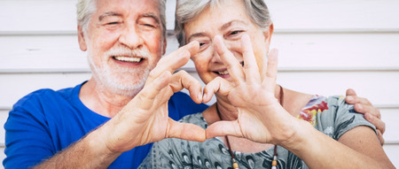 70 year old senior couple playing forming heart with hands. Happiness and joy together forever concept for old people man and woman - romantic and romance concept for relationship no age limit