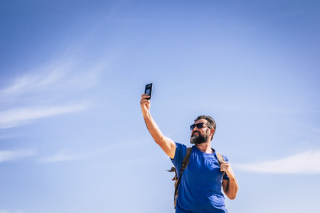 People and internet technology man with beard and sunlgasses loooking for signal with a mobile phone device - people traveling with backpack for adventure concept and alternative vacation - blue sky in background