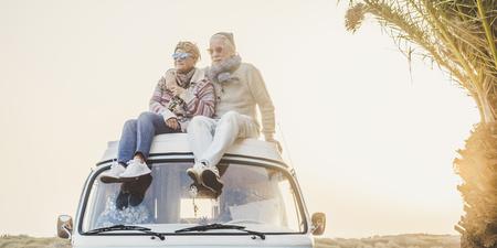 Wanderlust i koncepcja szczęścia w podróży ze starą starszą piękną parą siedzącą i cieszącą się wolnością na świeżym powietrzu na dachu zabytkowego pojazdu van razem - podświetlenie słońca