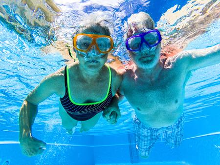 La pareja mayor de personas adultas se divierte nadando en la piscina bajo el agua con máscaras de buceo divertidas de colores - concepto de buceo y hombre y mujer activos jubilados disfrutando del estilo de vida - agua azul y adultos caucásicos