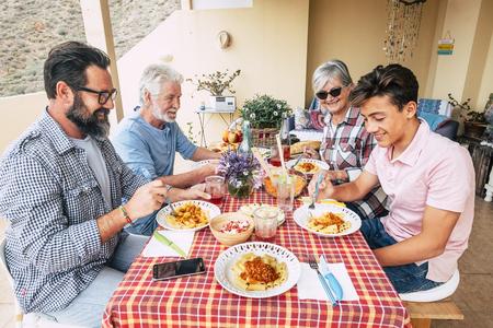 Familienmittagessen im Freien auf einem roten Tisch - Generationen gemischten Alters genießen und amüsieren sich mit italienischer Pasta auf der Terrasse zu Hause - Vater Großvater und Sohn