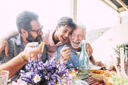 Il concetto di famiglia delle persone felici ride e si diverte insieme a tre diverse generazioni di età: nonno padre e figlio adolescente tutti insieme mangiando a pranzo