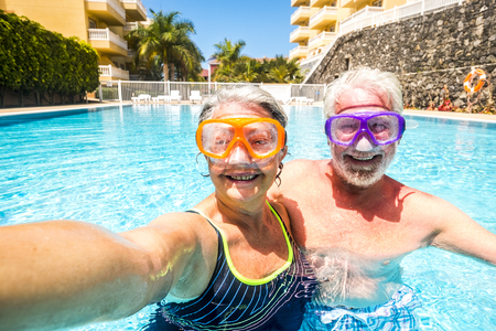 Happy cheerful people old senior man and woman have fun together in the summer swimming pool activity taking selfie pictures with scuba masks on the face for funny outdoor leisure activity in hotel holiday vacation