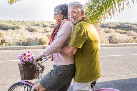 beautiful aged couple of senior in vacation go both on an old bike and enjoy the summer sunlight. tropical place and country side desert in background - concept or friendship and relationship for matures Foto de archivo