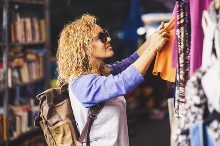Cheerful traveler young blonde curly woman looking and choosing clothes at the used market during alternative vacation - shopping lifestyle concept for nice people