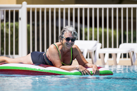 Happy cheerful caucasian people old senior woman lay down on coloured trendy lilo enjoying the swimmin pool outdoor leisure activity in summer time for vacation or relax in the city