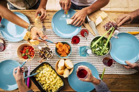Persone che mangiano insieme in amicizia o festa in famiglia con tavolo pieno di cibo visto dall'alto verticale - amici e concetto di divertimento - colori e sfondo con tavolo in legno Archivio Fotografico