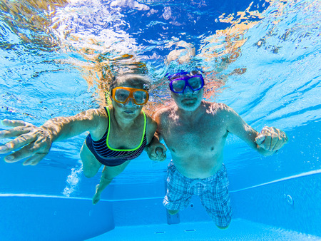 People have fun and enjoy swim underwater in the swimming pool with blue clear water around - summer holiday vacation resort hotel concept for tourists aged and retired - active old senior together