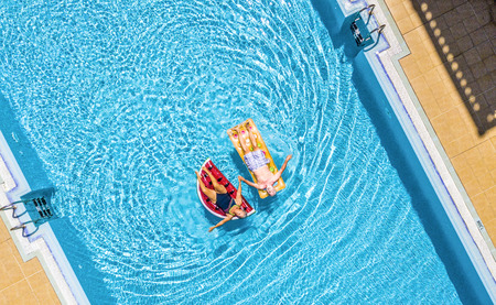 Aerial top vertical view of people old senior couple enjoying the retired lifestyle lay down with trendy coloured lilos inflatable mattress on a blue water clear swimming pool in resort hotel summer v