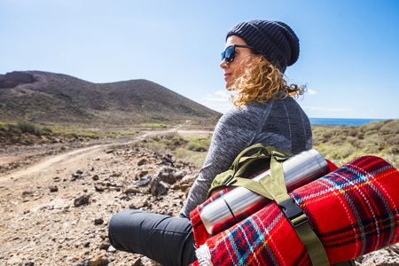 People and trekking backpack travel adventure activity - blonde woman sit down and rest looking at the beautiful scenic landscape with sea and valley enjoying the hiking leisure alone - alternative li