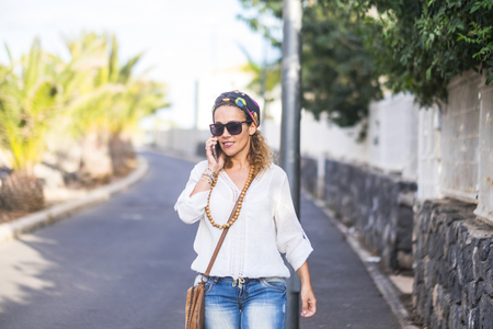 Hippy people portrait with attractive blonde middle age woman walking and calling at the phone on the street in outdoor leisure activity - happy people with chic fashion clothes using technology