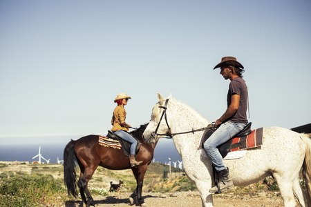 Happy caucasian couple of riders with horses. Outdoor, windmill in the background. Horizon over water