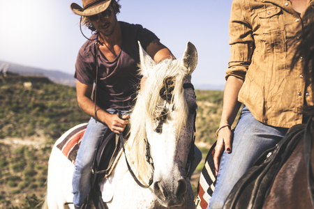 Couple of young alternative millennial man and woman riding horse in the nature - outdoor leisure activity for beautiful people with animals