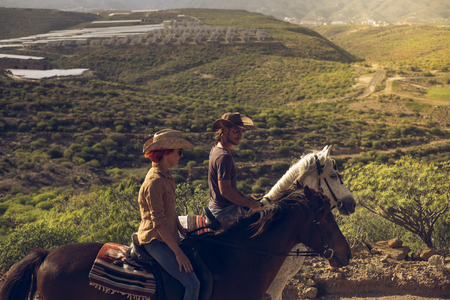Young people in outdoor leisure activity together in couple enjoying a riding on her horse brown and white on a beautiful mountain valley - people with animals concept of alternative lifestyle 写真素材