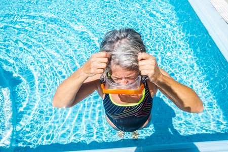 Silver society old active woman take diving mask to swim in the swimming pool and enjoy the summer time in clear blue water -  healthy lifestyle for retired mature people outdoor 写真素材