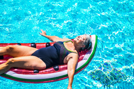 Happy beautiful aged senior lady enjoy the fresh water on a watermelon coloured lilo inflatable mattress on the blue water of swimming pool smiling and relaxing in a sunny day of summer