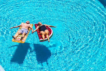 Total relax for happy mature senior retired people lay down on coloured lilos inflatable mattress on blue clear water of swimming pool in summer time - enjoying lifestyle and vacation 写真素材