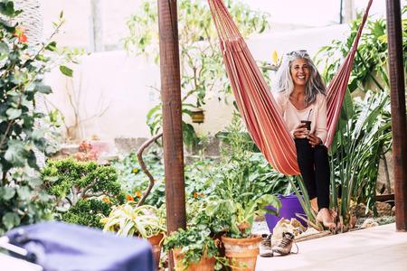 Fröhlich lächelndes Diversity-Menschenkonzept mit schöner trendiger erwachsener Frau mit weißem, langem Haar, die lachend auf einer Hängematte zu Hause im Garten einen Tee trinkt