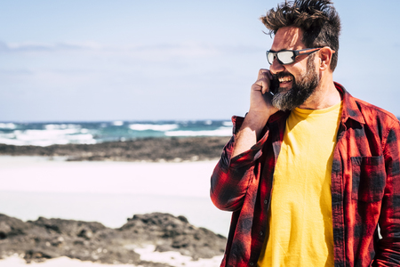 Cheerful happy hipster man with beard and sunglasses speaking at the phone with friends in outdoor beuaitufl place leisure activity - summer vacation concept with beach and ocean and sky in background 写真素材
